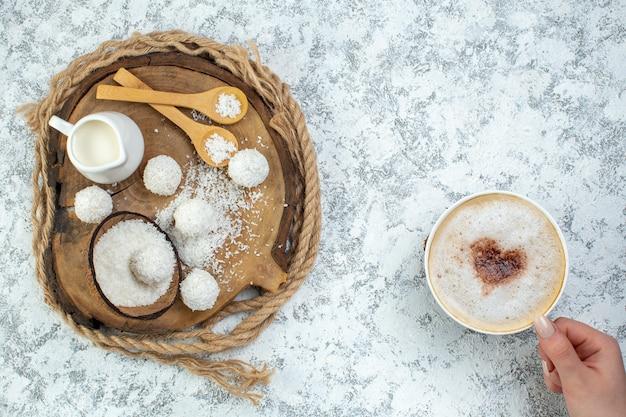 Bovenaanzicht cappuccino-kop in vrouwelijke hand kokospoeder kom kokosballen melkkom lepels op houten bord op grijs oppervlak