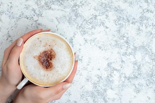 Bovenaanzicht cappuccino-kop in vrouwelijke hand op grijs oppervlak met kopieerplaats