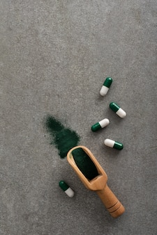 Bovenaanzicht capsules met houten lepel op tafel