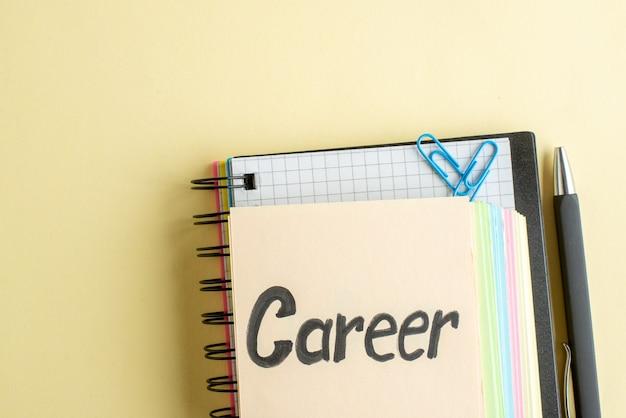 Bovenaanzicht carrière geschreven notitie met kleurrijke papieren notities op lichte ondergrond schrift kladblok zakelijk baan geld werk kantoor school bank pennen