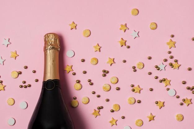 Bovenaanzicht champagnefles met confetti