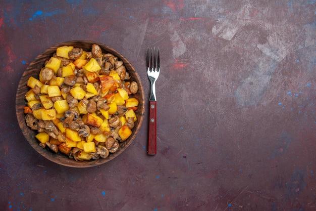 Bovenaanzicht champignons met aardappelen aan de linkerkant zijn er champignons met aardappelen in een kom op het donkere oppervlak