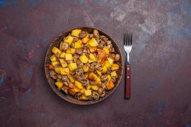 Bovenaanzicht champignons met aardappelen in het midden, er zijn champignons met aardappelen in een kom op het donkere oppervlak