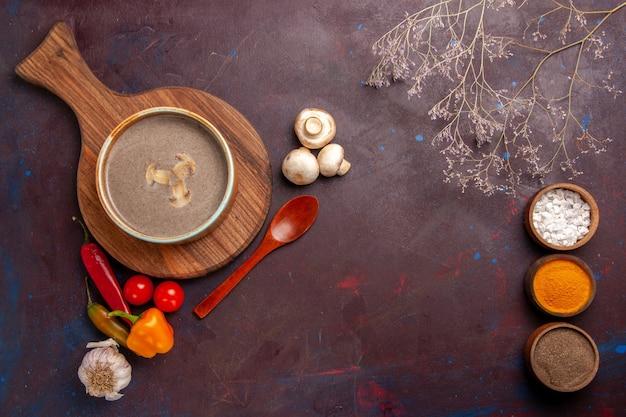Bovenaanzicht champignonsoep met verschillende kruiden op de donkere ruimte