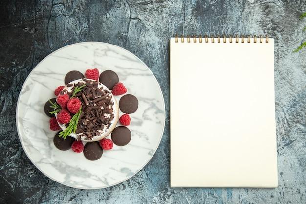 Bovenaanzicht cheesecake met chocolade en frambozen op witte ovale plaat kladblok op grijze ondergrond