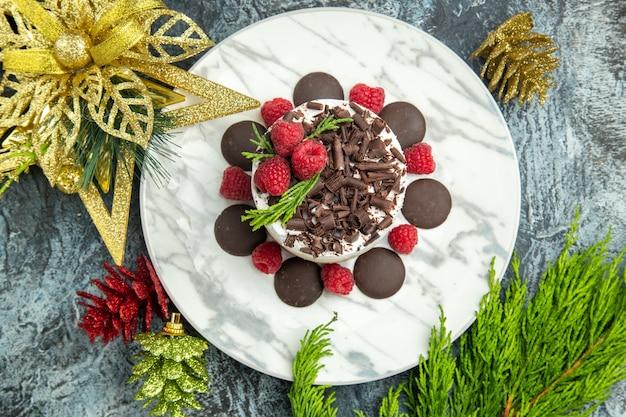 Bovenaanzicht cheesecake met chocolade en frambozen op witte ovale plaat xmas ornamenten op grijs oppervlak