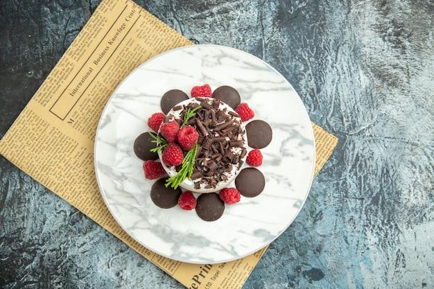 Bovenaanzicht cheesecake met chocolade en frambozen op witte ovale plateon krant op grijze oppervlakte vrije ruimte