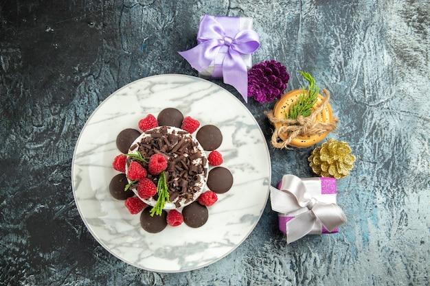 Bovenaanzicht cheesecake met chocolade op ovale plaat gebonden koekjes kerstcadeaus op grijze ondergrond