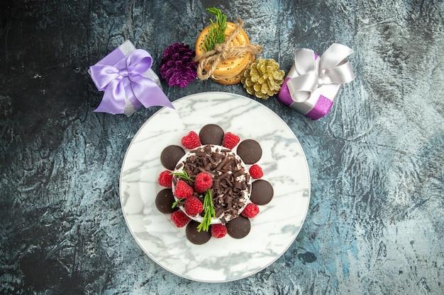 Bovenaanzicht cheesecake met chocolade op ovale plaat gebonden koekjes xmas ornamenten op grijs oppervlak