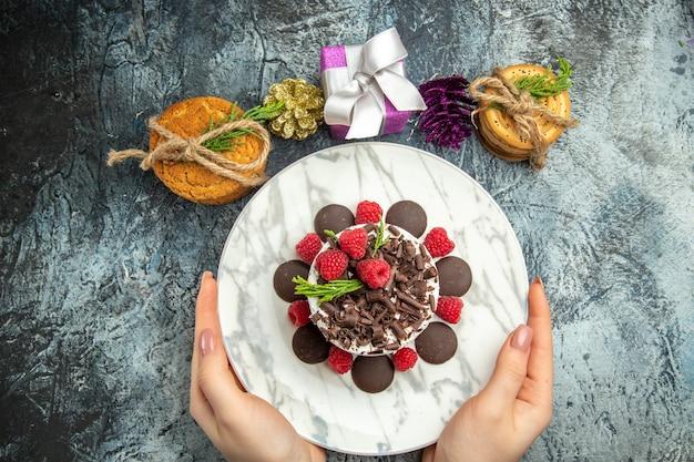 Bovenaanzicht cheesecake met chocolade op ovale plaat in vrouw handen koekjes xmas geschenken op grijze oppervlakte vrije ruimte