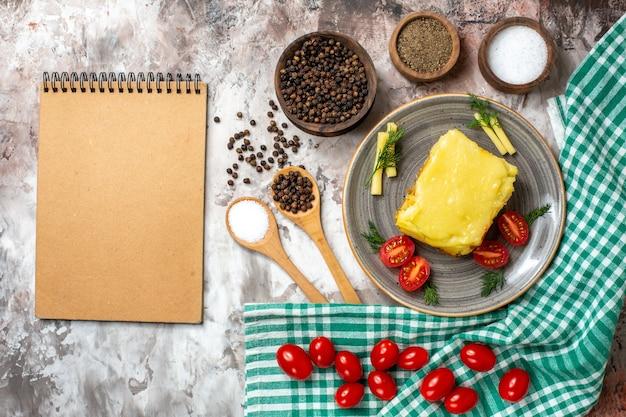 Bovenaanzicht cheesy brood tomaten op plaat verschillende kruiden in kommen houten lepels notitieblok op naakt