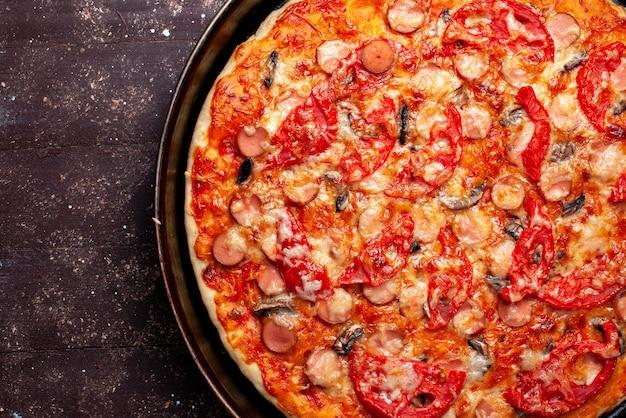 Bovenaanzicht cheesy tomaat pizza met olijven en worstjes in pan op bruin bureau, pizza eten maaltijd fastfood kaas worst