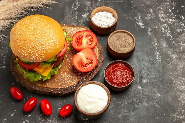 Bovenaanzicht cheesy vleesburger met kruiden op donkere bureaubroodje sandwich fastfood