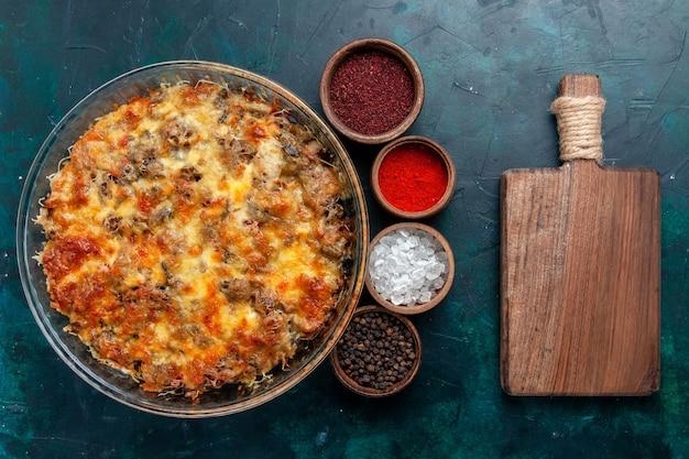 Bovenaanzicht cheesy vleesmaaltijd lekker bakken met kruiden op donkerblauw bureau eten vleesmaaltijd schotel plantaardig diner