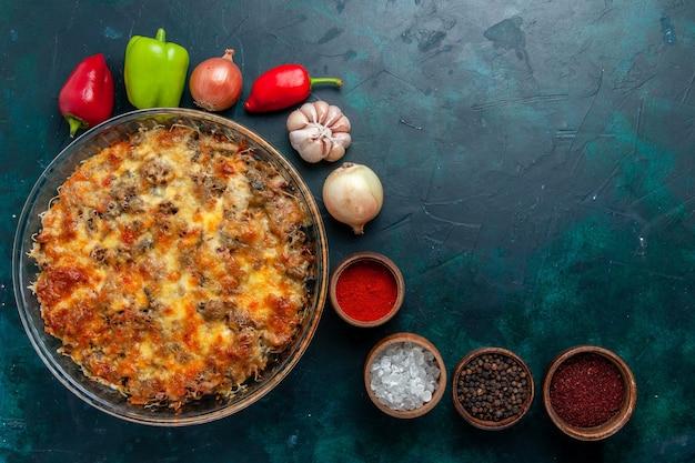 Bovenaanzicht cheesy vleesmaaltijd met verse groenten en kruiderijen op donkerblauw bureau eten vleesmaaltijd schotel plantaardig diner