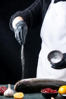 Bovenaanzicht chef-kok met handschoenen bestrooid met zout op verse vis granaatappel zaden in kom op tafel