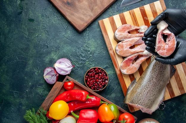 Bovenaanzicht chef-kok met plakjes rauwe vis op de keukentafel