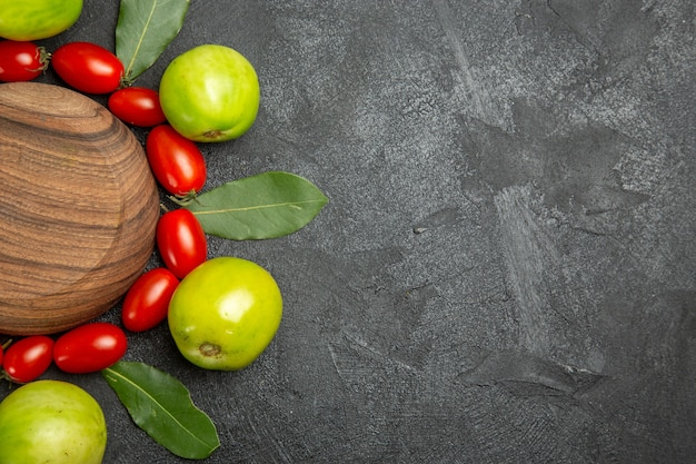 Bovenaanzicht cherry tomaten, groene tomaten en laurierblaadjes rond een houten plaat op donkere grond met kopie ruimte