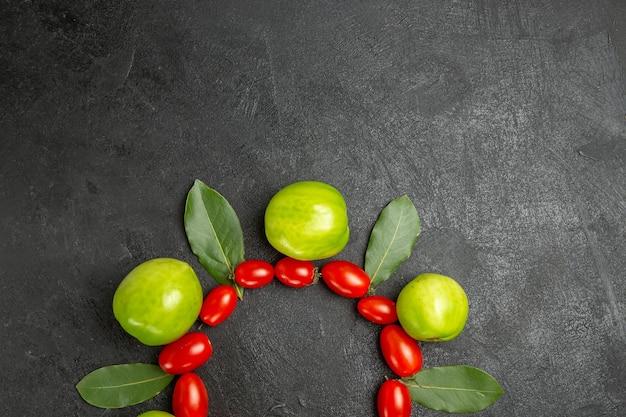 Bovenaanzicht cherrytomaatjes groene tomaten en laurierblaadjes op de bodem van donkere grond met vrije ruimte