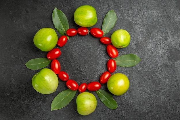 Bovenaanzicht cherrytomaatjes groene tomaten en laurierblaadjes op donkere grond met vrije ruimte