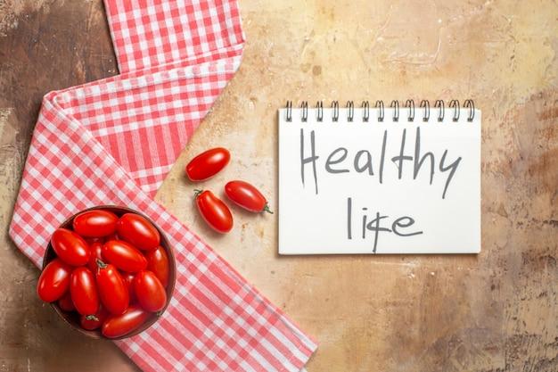 Bovenaanzicht cherrytomaatjes in houten kom een keukenhanddoek gezond leven geschreven op notitieblok op amberkleurige achtergrond