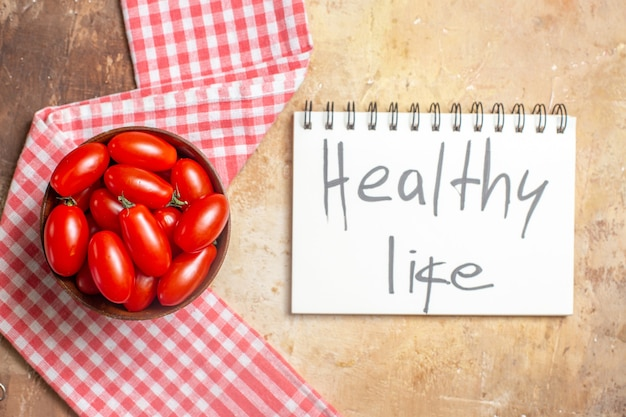 Bovenaanzicht cherrytomaatjes in houten kom een keukenhanddoek gezond leven geschreven op notitieboekje op amberkleurige achtergrond
