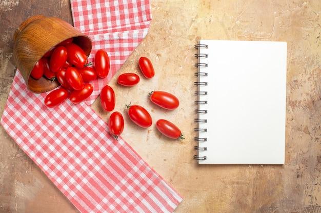 Bovenaanzicht cherrytomaatjes verspreid uit kom een theedoek een notitieboekje op amberkleurige achtergrond