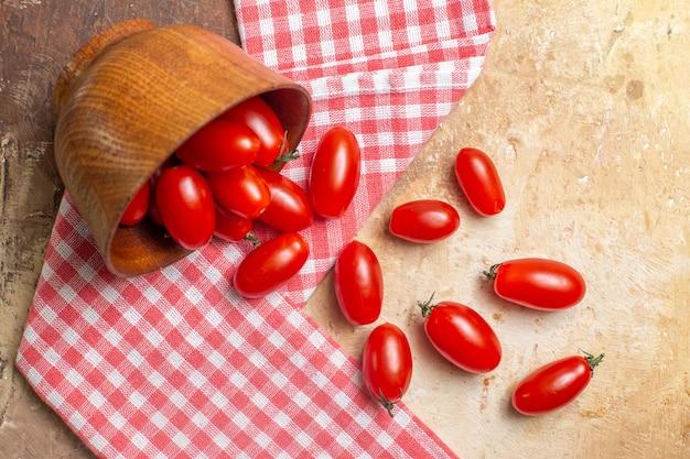 Bovenaanzicht cherrytomaatjes verspreid uit kom een theedoek op amberkleurige achtergrond