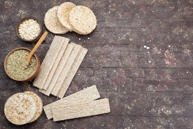 Bovenaanzicht chips en crackers lang en rond gevormd met gedroogde kruiden op hout