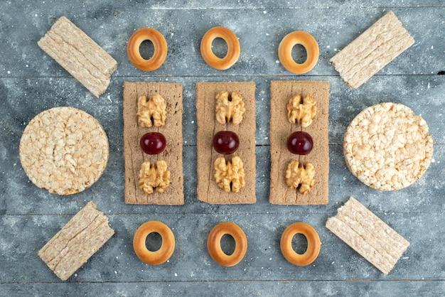 Bovenaanzicht chips en crackers met walnoten en kersen op grijs