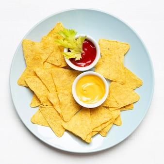 Bovenaanzicht chips en saus op plaat