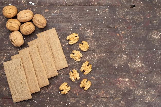 Bovenaanzicht chips en walnoten geïsoleerd op bruin