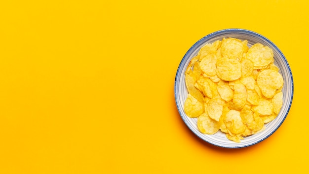 Bovenaanzicht chips kom op gele achtergrond