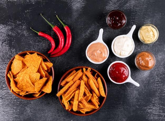 Bovenaanzicht chips met chili peper en sauses in kommen op zwarte steen horizontaal