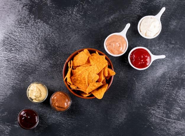 Bovenaanzicht chips met chili peper en sauzen in kommen en kopie ruimte op zwarte steen