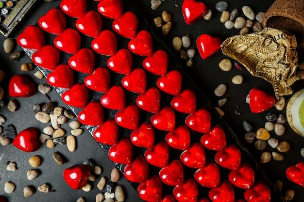 Bovenaanzicht chocolaatjes in de vorm van een rood hart op een standaard met steentjes