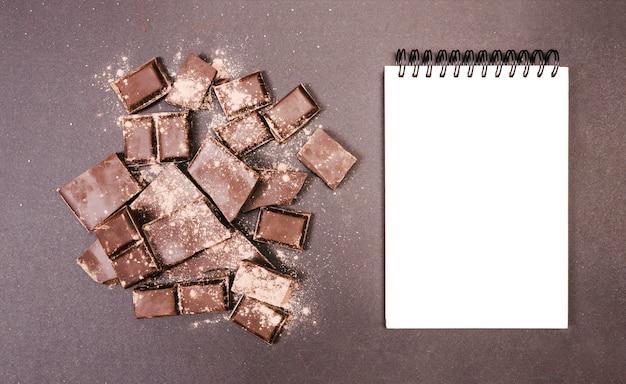 Bovenaanzicht chocolade bedekt met cacao met notitieboekje