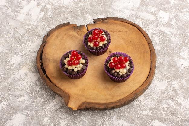 Bovenaanzicht chocolade brownies met veenbessen op het houten bureau en heldere backgroundk cake biscuit zoet bak deeg