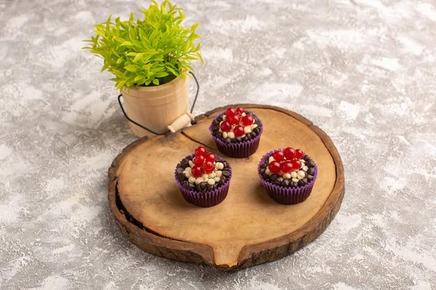 Bovenaanzicht chocolade brownies met veenbessen op het houten bureau met snoepjes en plant cake biscuit zoete bak deeg