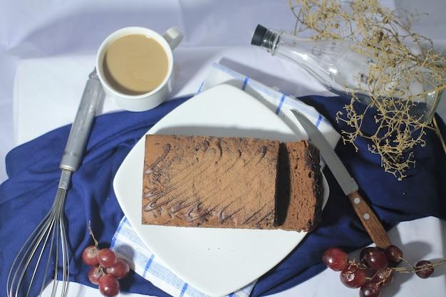 Bovenaanzicht chocolade brownies op een witte plaat met glas koffiedruif en mes eromheen