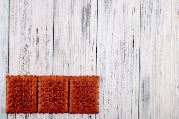 Bovenaanzicht chocolade crackers aan de linkerkant met kopie ruimte op witte houten achtergrond