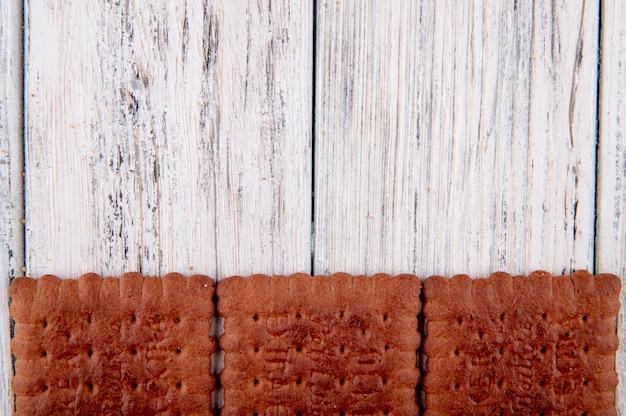 Bovenaanzicht chocolade crackers aan de onderkant met kopie ruimte op witte houten achtergrond
