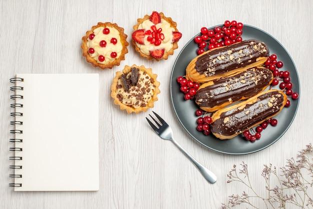 Bovenaanzicht chocolade-eclairs en aalbessen op de grijze plaat koekjes een vork en een notitieblok op de witte houten tafel