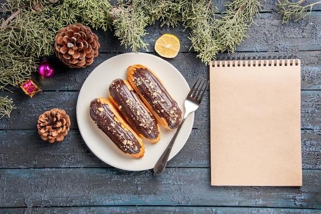 Bovenaanzicht chocolade eclairs en vork op witte ovale plaat kegels dennenboom bladeren kerst speelgoed schijfje citroen en een notitieblok op donkere houten tafel