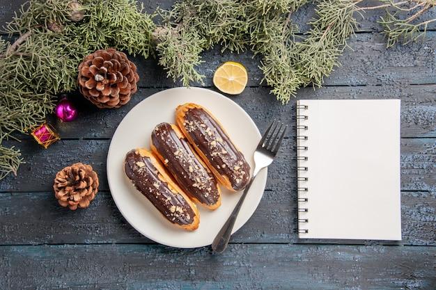 Bovenaanzicht chocolade eclairs en vork op witte ovale plaat kegels dennenboom bladeren kerst speelgoed schijfje citroen en een notitieboekje op donkere houten grond