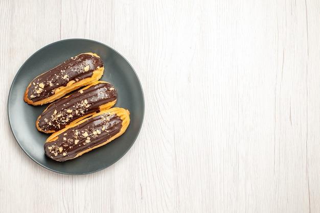 Bovenaanzicht chocolade-eclairs links boven op de grijze plaat op de witte houten ondergrond