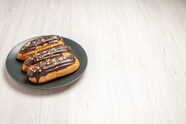 Bovenaanzicht chocolade-eclairs links boven op de grijze plaat op de witte houten ondergrond Gratis Foto