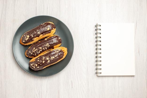 Bovenaanzicht chocolade-eclairs op de grijze plaat en een notitieboekje op de witte houten ondergrond