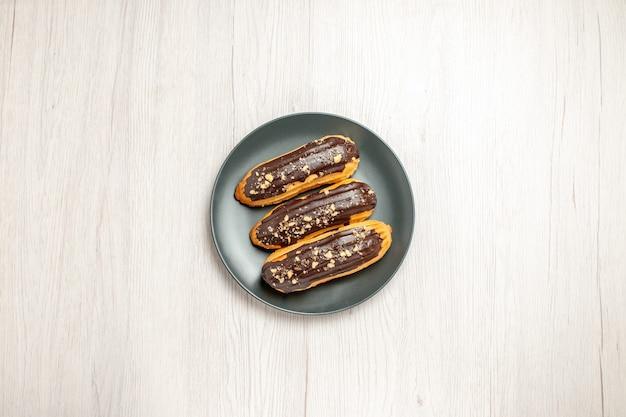 Bovenaanzicht chocolade-eclairs op de grijze plaat in het midden van de witte houten grond