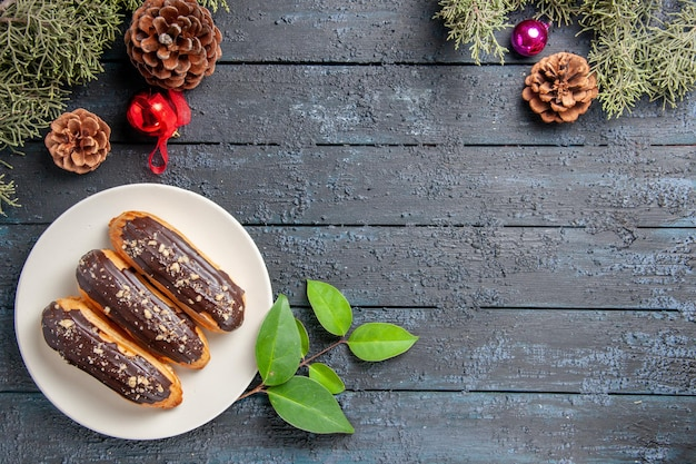 Bovenaanzicht chocolade eclairs op een ovale plaat kegels kerst speelgoed dennenboom bladeren en laurierblaadjes op donkere houten grond met vrije ruimte